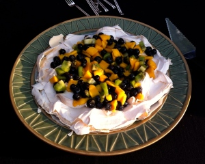 Pavlova topped with blueberries, mango & kiwi